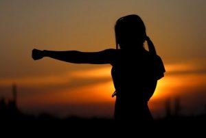 Silhouette of a woman with arm extended in from of a sunrise
